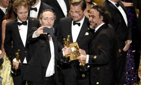 Emmanuel Lubezki, de izquierda a derecha, Leonardo DiCaprio y Alejandro G. Iñárritu se toman una selfie en el escenario tras la ceremonia de los Oscar.