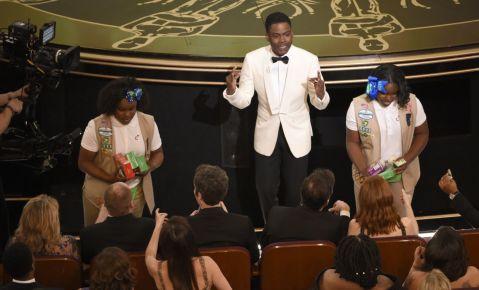 El presentador Chris Rock vende galletas de las Girl Scout al público en los Oscar.